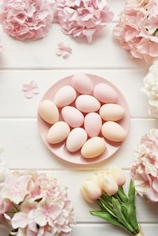 Marco hecho de flores de hortensia rosa y beige, huevos rosados y tulipanes amarillos