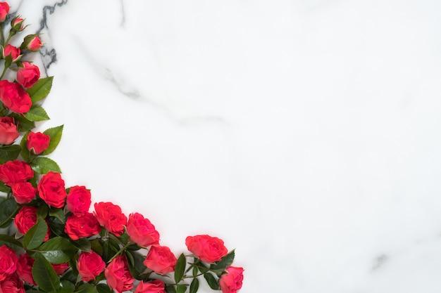 Marco hecho de flores rosas sobre fondo de mármol