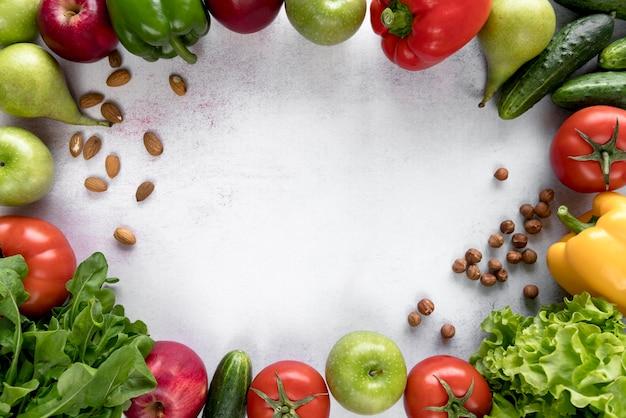 Marco hecho con frutas de colores; verduras y frutos secos sobre superficie blanca.