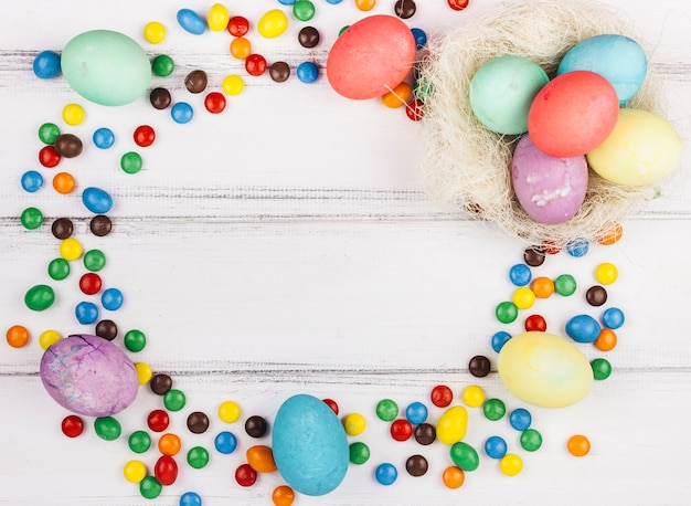 Marco hecho de huevos de pascua y caramelos pequeños.