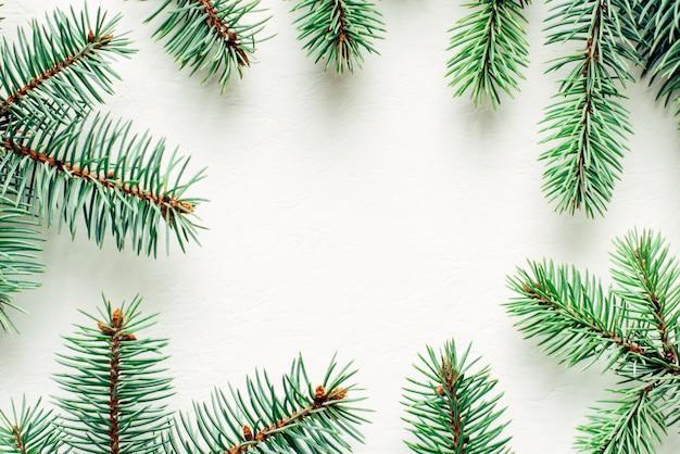 Marco hecho de ramas de abeto sobre fondo blanco. vista superior copia espacio.