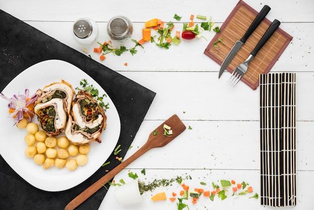 Marco hecho de rollo de carne y plato de ñoquis, vajilla y verduras.