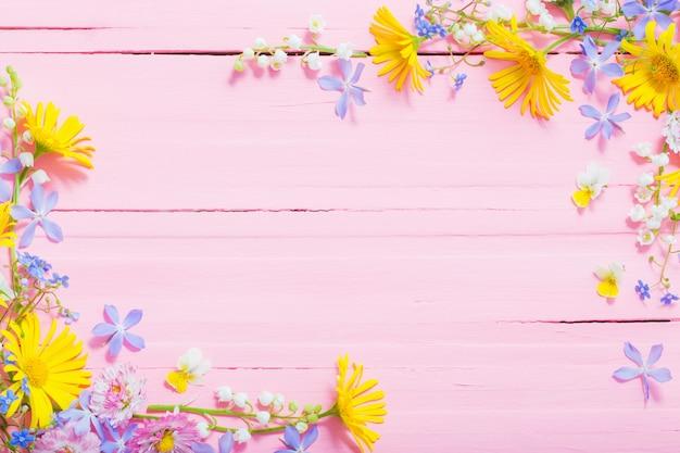 Marco de hermosas flores en madera rosa
