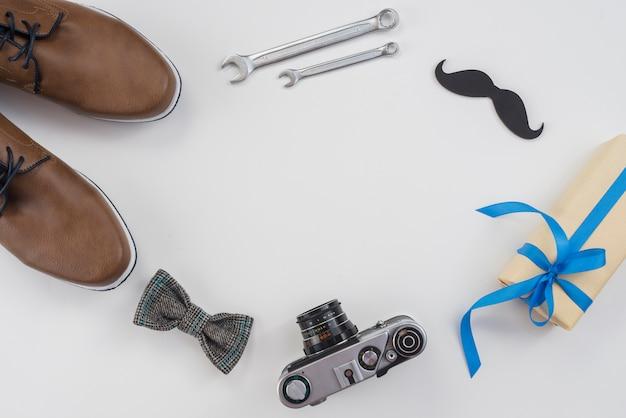 Marco de herramientas, cámara y zapatos de hombre en mesa.