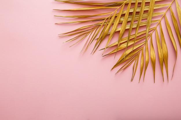Marco de hoja de palma dorada, textura de licencia tropical sobre fondo rosa con espacio de copia. el oro pintado deja espacio para el texto. fondo floral de verano.