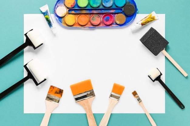 Marco de hoja de papel y paleta de colores de pintura