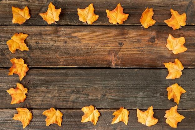 Marco de hojas amarillas sobre fondo de madera con espacio de copia