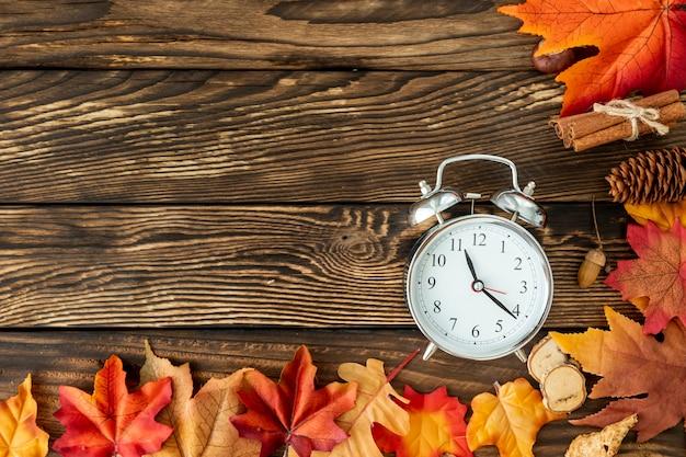 Marco de hojas coloridas con reloj