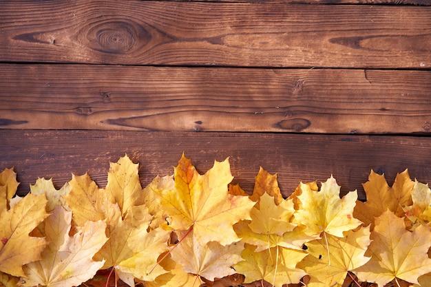 Marco de hojas de otoño sobre fondo de madera vista superior frontera de otoño hojas amarillas y naranjas mesa de madera vintage copia espacio para texto