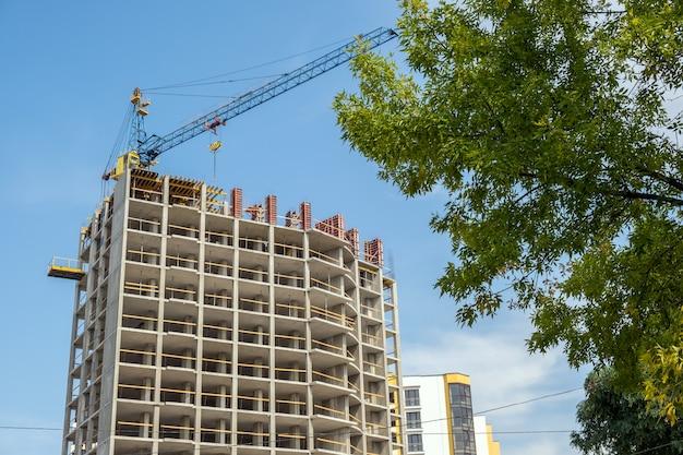 Marco de hormigón de alto edificio de apartamentos en construcción y grúa en una ciudad.