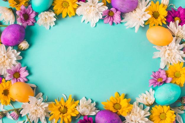 Marco de huevos brillantes y capullos de flores