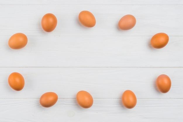Marco de huevos de gallina marrón en mesa