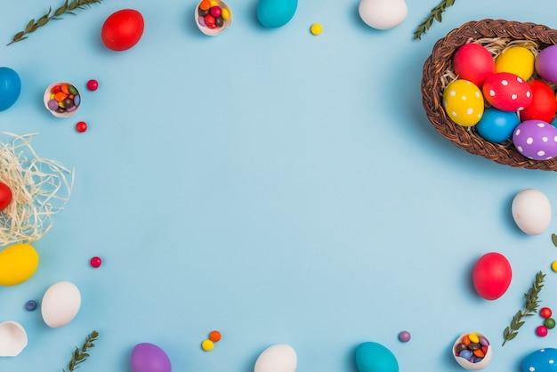 Marco de huevos de pascua y cesta en mesa