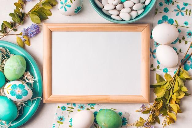 Marco entre los huevos de pascua en un plato cerca de pequeñas piedras en un tazón y ramitas de flores