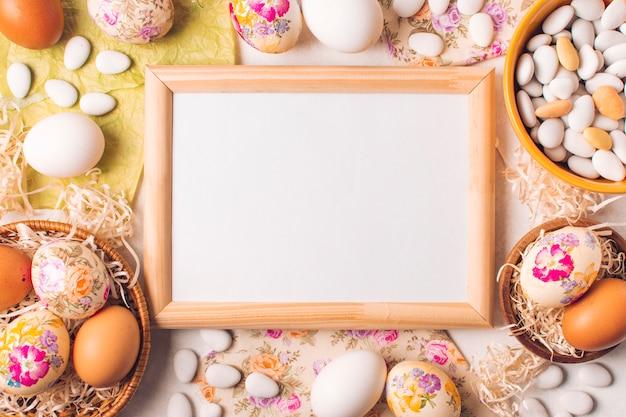 Marco entre los huevos de pascua en platos y pequeñas piedras en un tazón