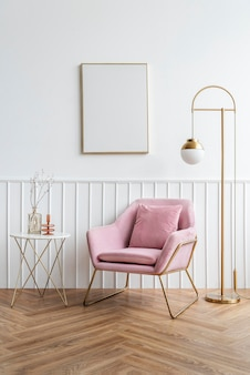 Marco de imagen en blanco junto a un sillón de terciopelo rosa