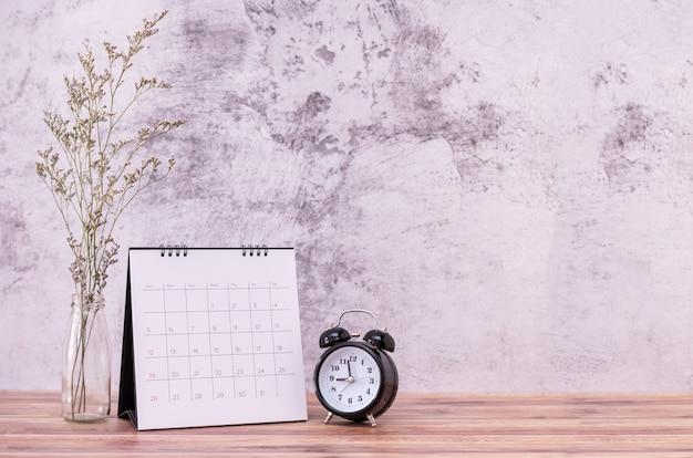 Marco de imagen y flores y reloj de mesa de madera.