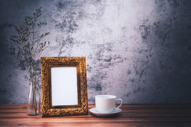 Marco de imagen y flores y tazas de café en la mesa de madera