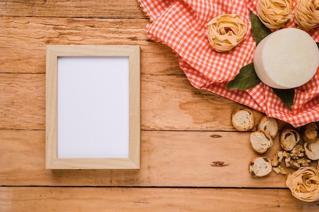 Marco de imagen vacío cerca de comida sabrosa con mantel a cuadros sobre mostrador de madera
