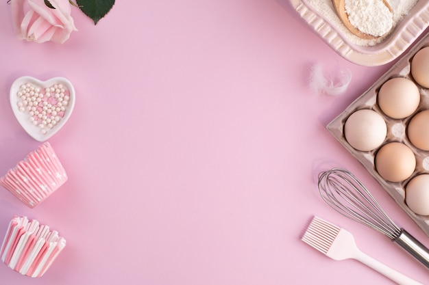 Marco de ingredientes alimentarios para hornear sobre un fondo pastel ligeramente rosa. cocinar en plano con espacio de copia. vista superior. concepto de horneado. endecha plana