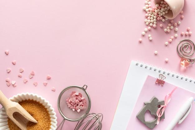 Marco de ingredientes alimenticios para hornear en un pastel suavemente rosa. concepto de horneado