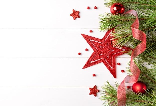 Marco de luz de navidad decorado con adornos rojos y blancos, cinta y estrella grande. copiar espacio en el borde
