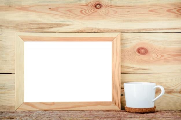 Marco de madera aislado con las decoraciones de una taza blanca en un fondo de madera.