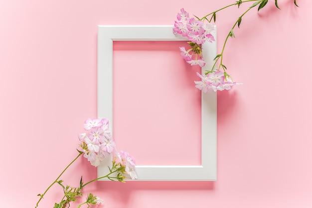 Marco de madera blanca y flores sobre fondo rosa con espacio de copia.