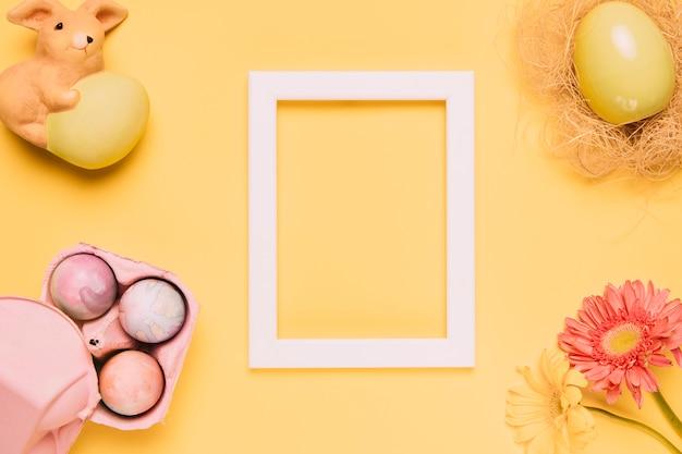 Marco de madera blanco en blanco con huevos de pascua; estatuilla de conejo y flor de gerbera sobre fondo amarillo