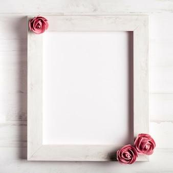 Marco de madera en blanco con hermosas rosas