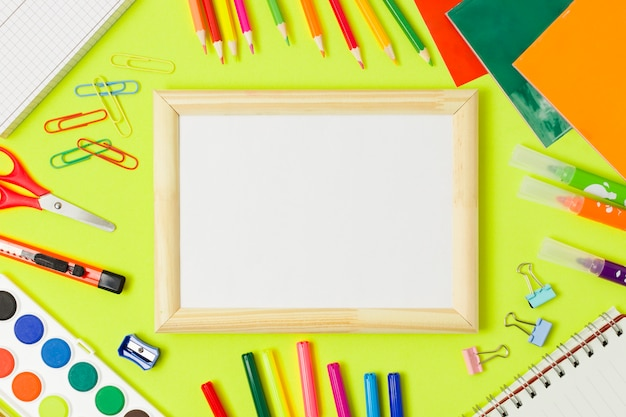 Marco de madera en blanco y útiles escolares