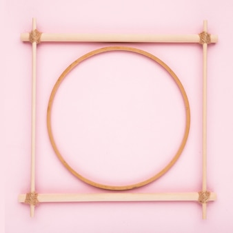 Un marco de madera circular y cuadrado vacío sobre fondo rosa