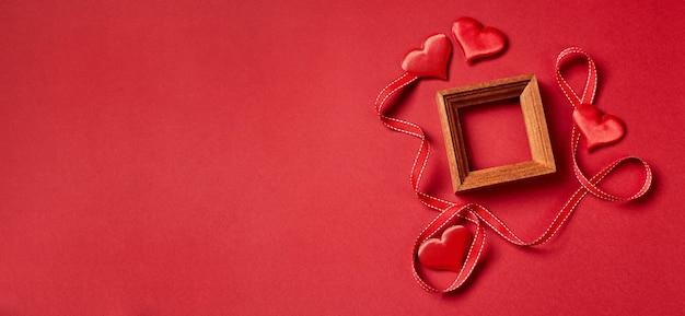 Marco de madera y corazones y decoraciones del día de san valentín sobre fondo rojo. vista superior con espacio de copia. concepto de san valentín.