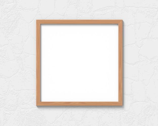 Marco de madera cuadrado que cuelga en la representación de la pared 3d.