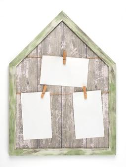 Marco de madera con cuerdas y hojas de papel blanco vacías colgadas en pinzas de madera