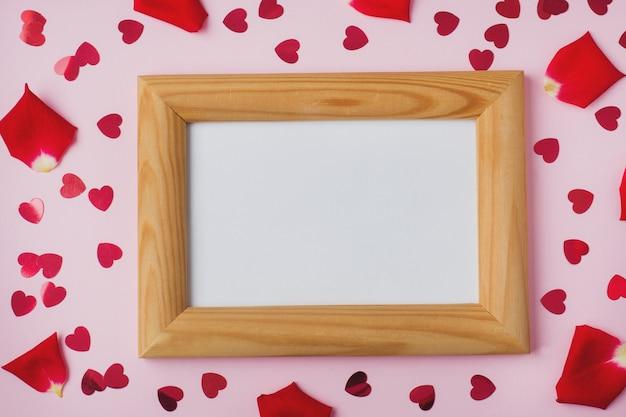 Marco de madera con espacio para texto, pétalos de rosa y corazones rojos.