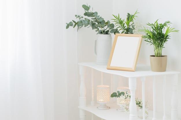 Marco de madera en estante blanco vintage con flores y plantas.