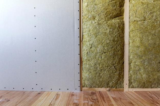 Marco de madera para futuras paredes con placas de yeso aislado con lana de roca y personal aislante de fibra de vidrio para barrera de frío. cómodo y cálido concepto de hogar, economía, construcción y renovación.