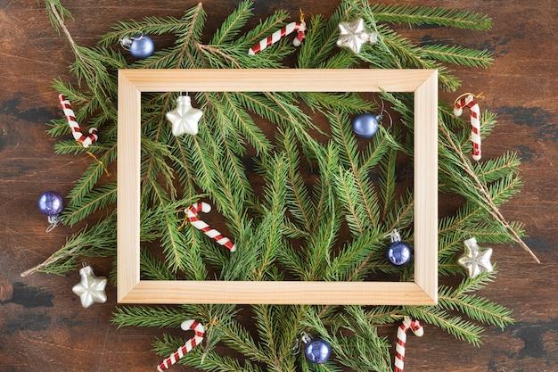 Marco de madera hecho de ramas de abeto y adornos navideños en madera oscura
