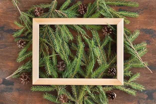 Marco de madera hecho de ramas de abeto y adornos navideños en madera
