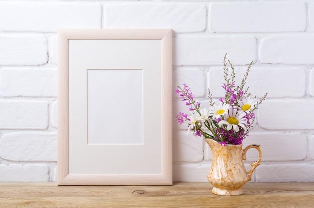 Marco de madera con manzanilla y flores de color púrpura en jarra dorada