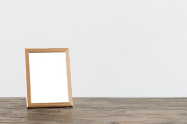 Marco de madera en mesa de madera sobre superficie blanca