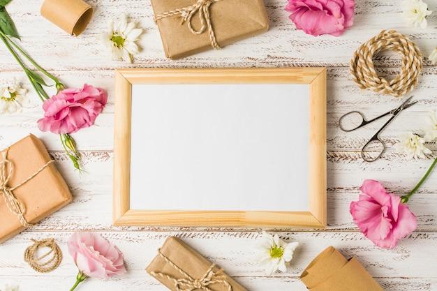 Marco de madera; regalos; eustoma rosa flores y tijera sobre superficie de madera