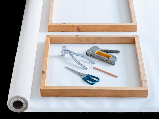 Marco de madera sobre lienzo de algodón de artista blanco con herramienta para preparar el estiramiento