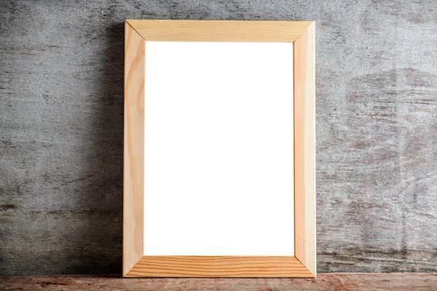 Marco de madera en una tabla de madera en una pared gris.
