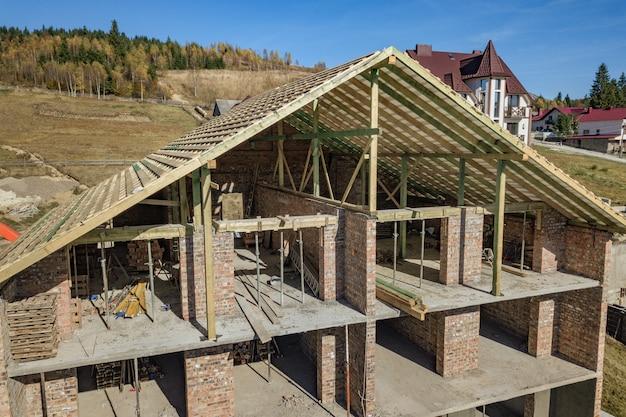 Marco de madera de techo nuevo en una casa grande de ladrillo en construcción.