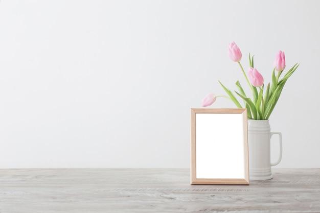 Marco de madera y tulipanes rosados en florero de cerámica blanca sobre fondo de pared blanca