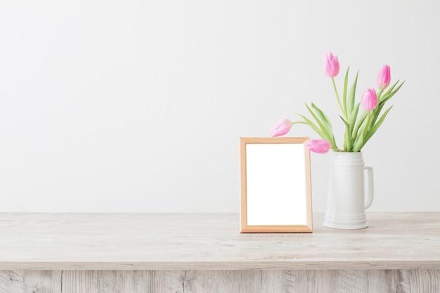 Marco de madera y tulipanes rosas en jarrón de cerámica blanca sobre pared blanca