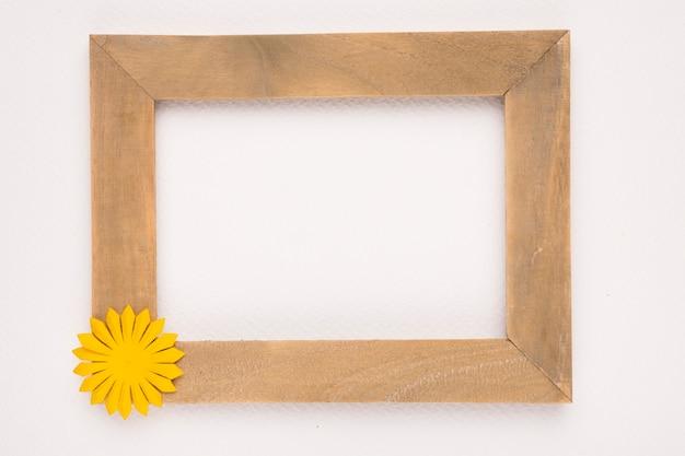 Marco de madera vacía con flor amarilla sobre fondo blanco