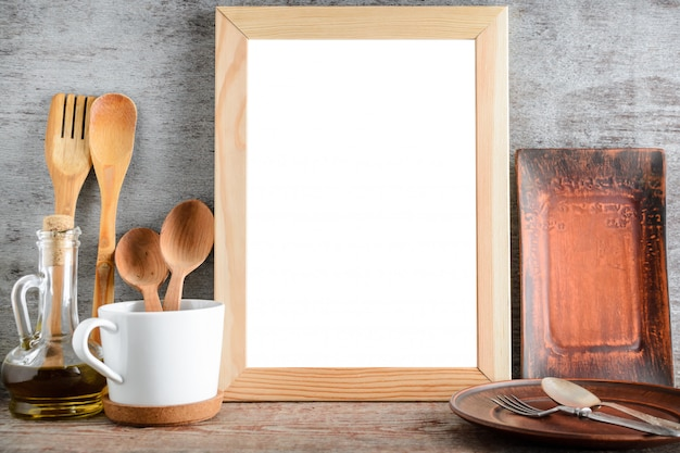 Marco de madera vacío y accesorios de cocina en la mesa